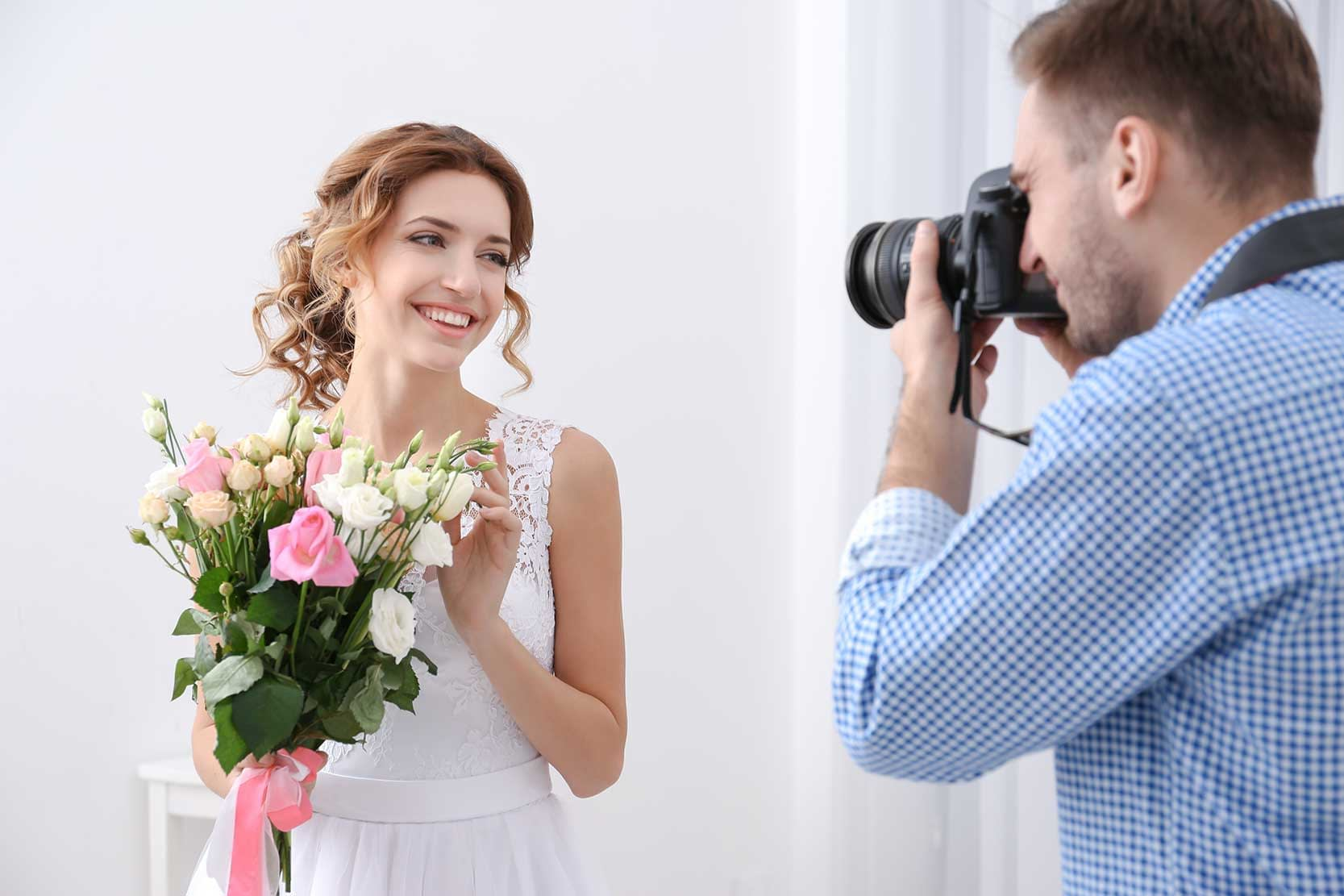 A wedding photographer taking a photo of a bride